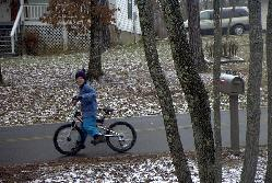 My son Brent rides the bike he got for Christmas in 2003 out on the street.  Sean Puckett, 2003